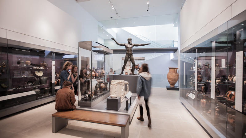 A gallery inside the Ashmolean Museum in Oxford showing people viewing a sculpture and objects in display cases.
