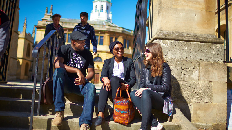 A group of people sitting on the sandstone steps of an Oxford landmark.