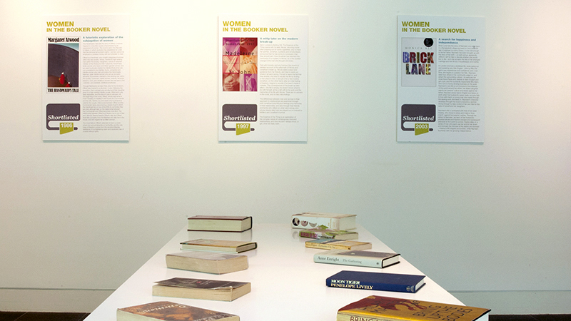 Display of books on a table with information boards behind.