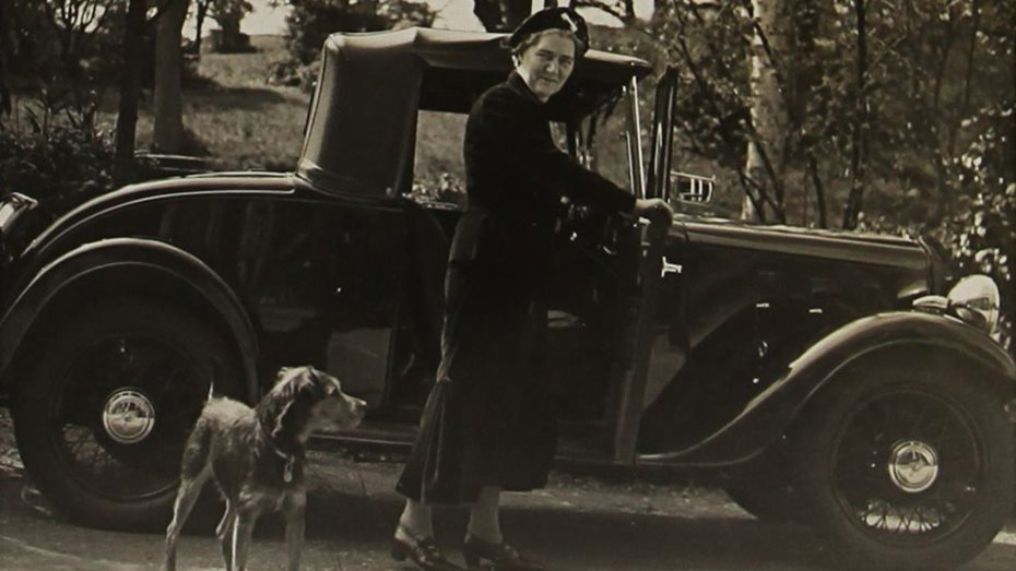 Elizabeth Casson and her dog Bran stand next to a car