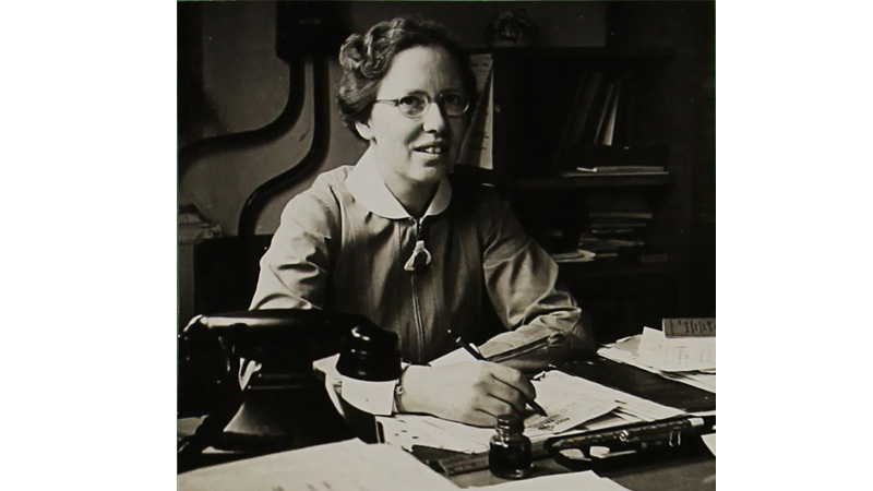 Mary Macdonald sitting at a desk.