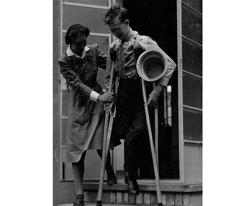 Black and white photograph of an occupational therapy student helping a man on crutches to walk down a step.