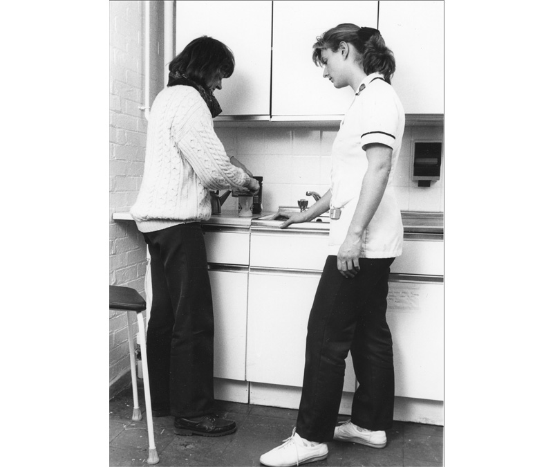 Black and white photograph of an occupational therapy student standing with a patient while she makes a hot drink.