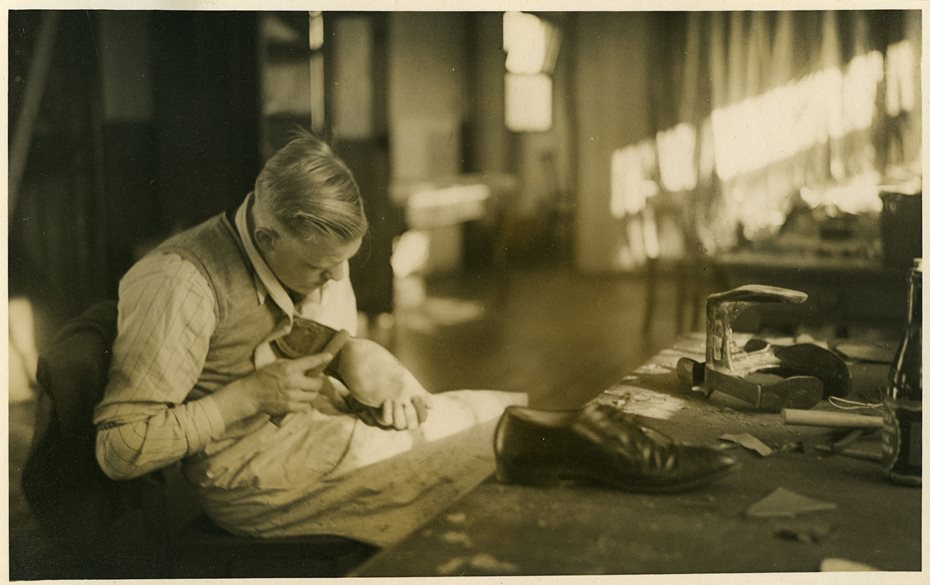Sepia photograph of a man making a shoe.