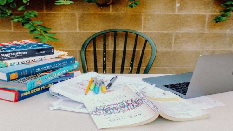 Outdoor study scene with chair, table, books and laptop