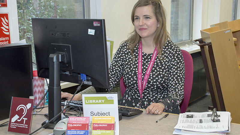 A member of Library staff sitting at the Harcourt Hill enquiry desk.