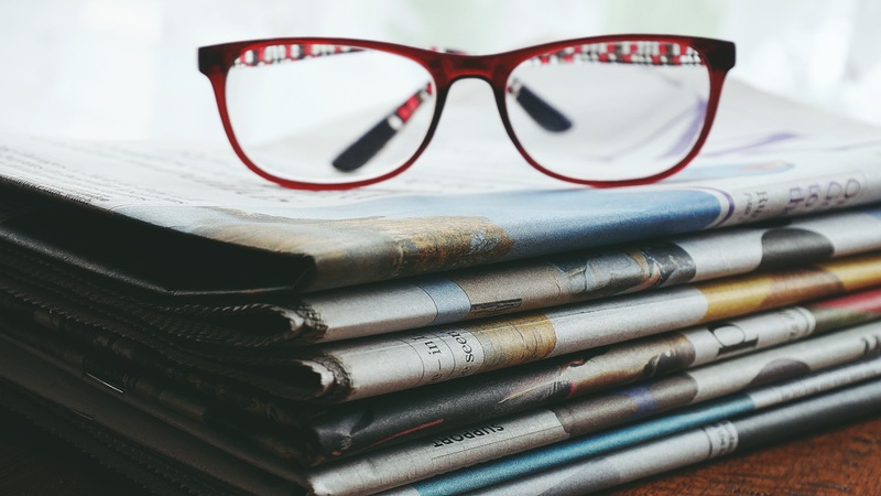 Pair of glasses on top of folded newspapers