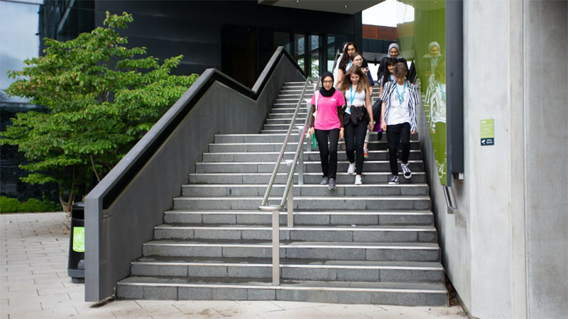 Students walking down external staircase