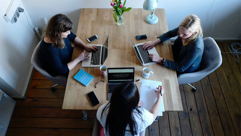 Three women sitting at a table working on laptops