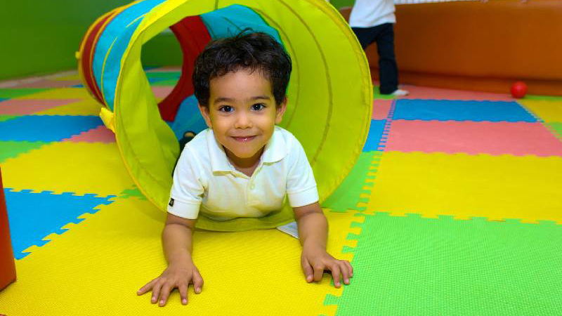 Small child playing in a tunnel at nursery