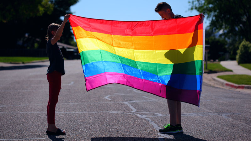 Two people holding up a rainbow flag in a sports ground