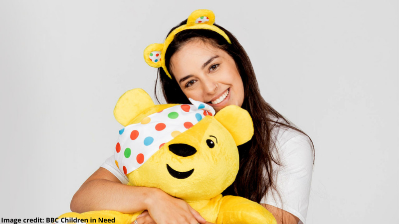 Rosie, a white woman with long brown hair wearing Pudsey ears hugs a Pudsey Bear